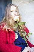 picture of girl next door  - Woman smelling white rose next to stain door - JPG