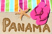 Panama beach travel concept background. PANAMA written in sand with water next to beach towel, summer sandals and starfish. Summer and sun vacation holidays conceptual image.