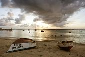 Sint Michiel, Curacao - November 16, 2014: Locals swimming and having fun in the sea at Sint Michiel bay; some fishing boats are moored, others laying on the beach.