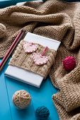 image of blanket snow  - One old notebook in knitted cover with felt hearts lie next to the coil bright filaments and blanket knitted on blue background - JPG