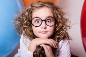 Portrait Of Surprised Curly Teen Girl In Glasses On The Background Of Large Rubber Balls.