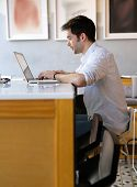 foto of internet-cafe  - Portrait of a young man typing on laptop at internet cafe - JPG