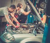 Two mechanics fixing car in a workshop