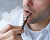image of exhale  - Close up part face of young man exhaling smoke from electric cigarette - JPG