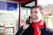 picture of phone-booth  - Portrait of a young man calling from phone booth - JPG