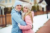 Young dates in winterwear embracing in urban environment