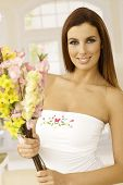 Attractive young woman holding bouquet of flowers in hand, smiling happy.