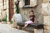 Little Girl Sitting On An Old Wooden Bench