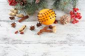 Orange with spices, rowan, and Christmas pine sprig on color wooden background