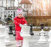 Chess game with giant chess piece. Girl playing strategic outdoor game