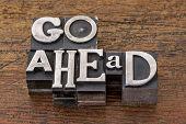 go ahead words in mixed vintage metal type printing blocks over grunge wood