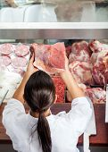 High angle rear view of female butcher holding red meat at butchery counter