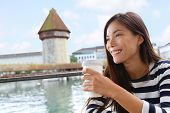 Woman drinking coffee at cafe in Lucerne, Switzerland. Casual girl tourist on travel visiting landmarks tourists attraction Kapellbrucke Chapel Bridge with Wasserturm water tower on Reuss River.