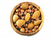 Top view of almonds and nuts in a handmade wooden bowl isolated on white background.