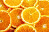 stock photo of valencia-orange  - background made of many sliced juicy oranges - JPG