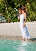 Beautiful woman walking along seaside on tropical beach