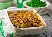 Baked Pudding With Fish And Mushrooms In A Ceramic Form For Roasting And Green Peas In A Bowl.