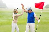 image of 5s  - Golfing couple high fiving on the golf course on a foggy day at the golf course - JPG