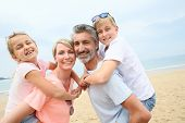 pic of piggyback ride  - Parents giving piggyback ride to children at the beach - JPG