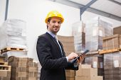pic of warehouse  - Warehouse manager wearing hard hat using tablet in a large warehouse - JPG