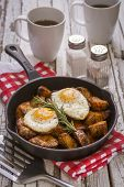 picture of baked potato  - Seasoned baked potatoes in a black cast iron frying pan with a sprig of rosemary on a wooden table top with a red and white checkered pattern dish towel salt and pepper shakersa cup of black coffee two fried eggs and a spatula - JPG