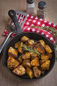 foto of baked potato  - Seasoned baked potatoes in a black cast iron frying pan with a sprig of rosemary on a wooden table top with a red and white checkered pattern dish towel salt and pepper shakersa cup of black coffee and a spatula - JPG