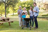 picture of extended family  - Extended family having a barbecue on a sunny day - JPG