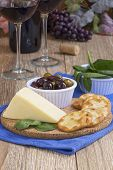 picture of kalamata olives  - A rustic wooden table setting with a wedge of white cheddar cheesecrackerskalamata olives spinich leaves with two glasses of red wine a wine bottle and wine bottle cork - JPG