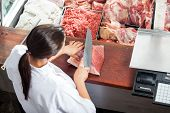 foto of slaughterhouse  - High angle rear view of female butcher cutting red meat at butchery - JPG