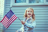 pic of waving  - Pretty little girl with long curly blond hair smiling and waving american flag - JPG