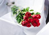 stock photo of banquet  - Bouquet of red roses laying at the decorated with white cloth banquet chair - JPG