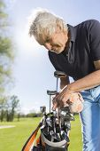 image of golf bag  - Close up of friendly senior golf player pulling out golf club from bag - JPG
