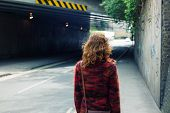 pic of underpass  - A young woman is walking on the street near an underpass - JPG