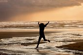 picture of leaping  - A girl in silhouette at sunset leaps into the creek on Nye Beach that flows into the ocean in Newport Oregon - JPG