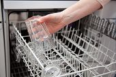 stock photo of dishwasher  - Woman putting glass in the dishwasher - JPG