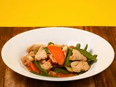 stock photo of stir fry  - chicken stir fry thai style on a yellow background on a wood table - JPG