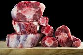picture of cutting board  - Fresh and raw oxtail cut on the cutting board isolated on a black background - JPG