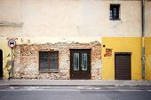 stock photo of windows doors  - Old weathered street wall with some windows and doors - JPG