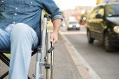 stock photo of wheelchair  - Detail of a man using a wheelchair in an urban street - JPG