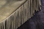 foto of buckskin  - A close up photo of an old buckskin leather cowboy coat with fringe - JPG