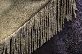 picture of buckskin  - A close up photo of an old buckskin leather cowboy coat with fringe - JPG