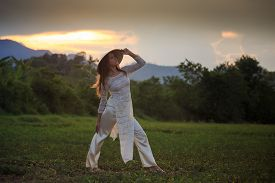 foto of long distance  - slim blonde girl in Vietnamese national white long dress and hat looks into distance on field against sky at sunset