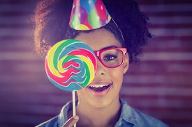 stock photo of lollipops  - Portrait of a hipster hiding herself behind a lollipop against a brick wall - JPG