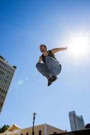 picture of parkour  - Man doing parkour in the city on a sunny day - JPG