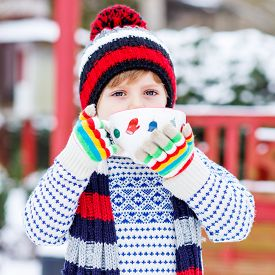 pic of cold drink  - Little boy drinking chocolate drink with marshmallows outdoors with snow background - JPG